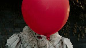 Clownen döljer halva ansiktet bakom en ballong.