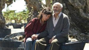 Alma (Anna Castillo) sitter vid ett olivträd tillsammans med sin farfar Ramón (Manuel Cucala).