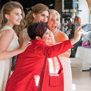 Sari Kaasinen punaisessa mekossa kännykkäkolmen valkoasuisen tyttärensä ympäröimänä
