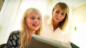 Naiset selailevat valokuva-albumia.