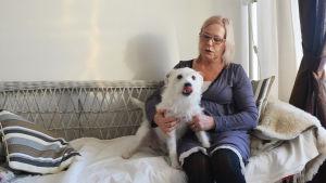 En kvinna sitter i en soffa och håller om en liten vit hund. Kvinnan tittar på hunden som slickar sig om munnen.