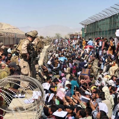 Finländska soldater står på en mur på Kabuls flygplats. På marken står en större folkmassa.