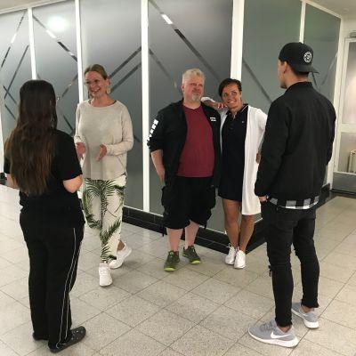 Kaksi nuorta ja kolme aikuista seisovat juttelemassa.