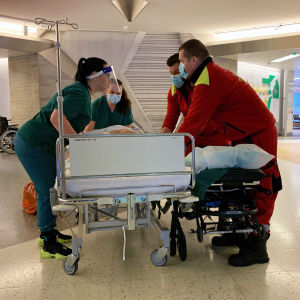 Sjukvårdspersonal transporterar en patient i sin säng i en korridor.