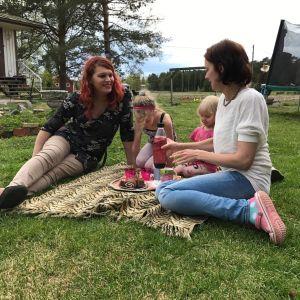 Familjen Wiklund har picknick på en filt på gräsmattan.