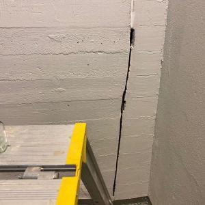 Halkeama seinässä ja kittaajan käyttämä rakennusteline.