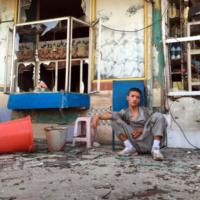 En chockad pojke sitter intill attentatsplatsen på lördagen 23.7.2016