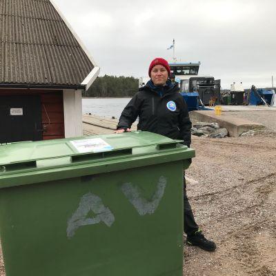 Linda Johansson vid ett avfallskärl på Själö med M/S Roope i bakgrunden