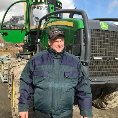 Christian Blomqvist står framför sin stora skogsmaskin