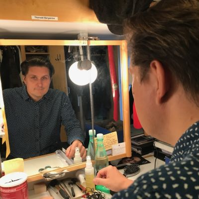 Thorvald Bergström tittar in i kameran via spegeln på hans sminkbord.