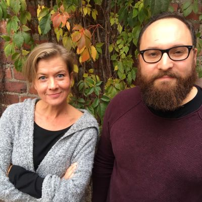 Jeanette Björkqvist och Simo Levanto poserar framför en tegelvägg.