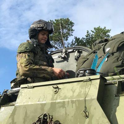 Finländsk rekryt uppe på bepansrat militärfordon.
