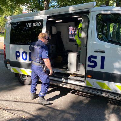 Poliisi sulkemassa poliisiauton liukuovea