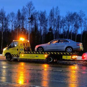 Hinausauto ottaa henkilöautoja kyytiinsä tien varressa.