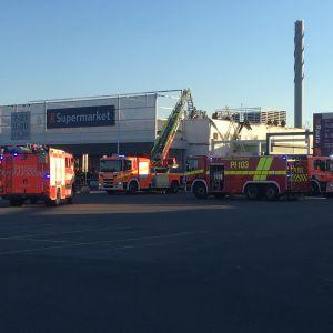 Useita pelastuslaitoksen yksiköitä sammutustöissä Tampereen Nekalan K-Supermarketin pihassa lauantai-iltana 3. heinäkuuta 2021.