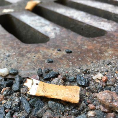 Tupakantumppi lojuu maassa sadevesiviemärin vieressä