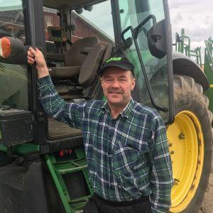 En medelålders man med keps på huvudet står bredvid en traktor.