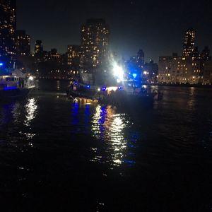 Räddningarbetare från brandkåren i New York intill helikoptervraket i East River, New York.