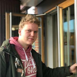 Nuori mies avaamassa koulun pääovea ulkopuolelta