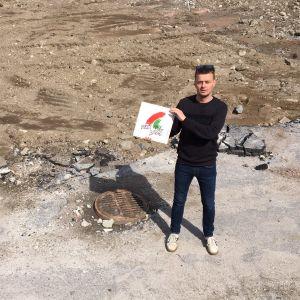 En man står på marken med en lp-skiva.