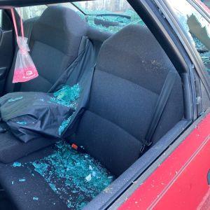 Auto, jonka ikkunat on rikottu ja sirpaleita on levinnyt auton sisäosaan.