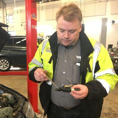 Tomi Harkka tarkistaa, mitä nesteitä auto on syönyt.