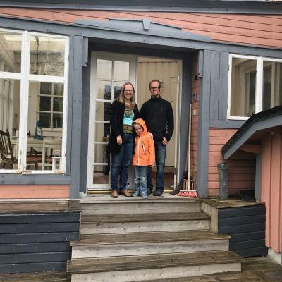 Anna, Arvid och Magnus Dahlbacka på trappan till deras hus.