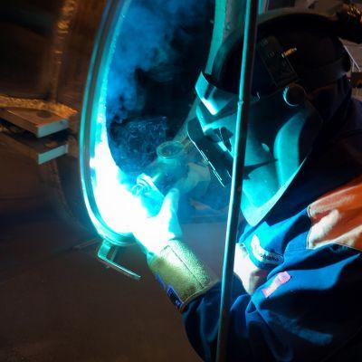 Työntekijä hitsaa tankin alumiinirunkoa.