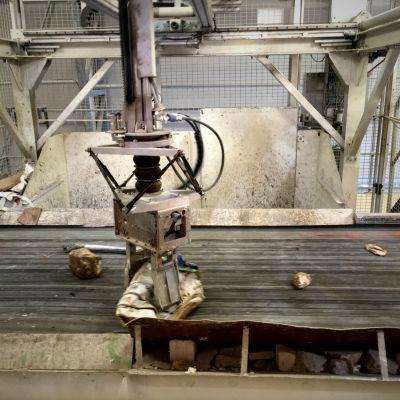 Robottikäsi nostaa rakennusjätteen kappaleita liukuhihnalta siiloihin.