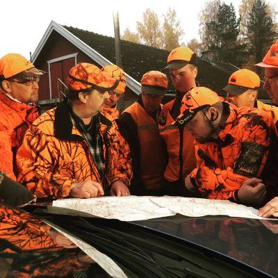 oranssiasuisia hirvimiehiä tutkimassa karttaa auton konepellillä
