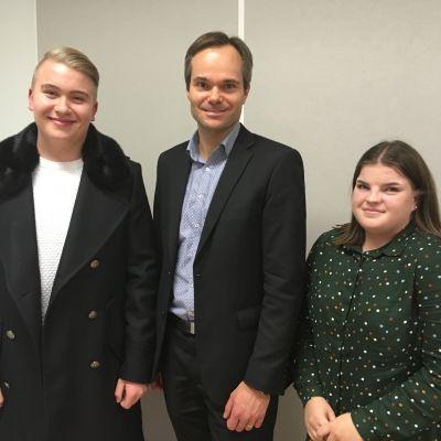 Yhteiskuvassa lukiolainen Tiitus Keijonen, sisäministeri Kai Mykkänen sekä lukiolainen Emma Mäenpää