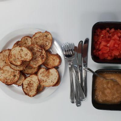 Köyhiä ritareita, hilloa ja paloiteltua vesimelonia. Kuvassa on myös haarukoita ja veitsiä.