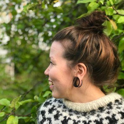 Anna Vihervalli seisoo omenapuun alla.