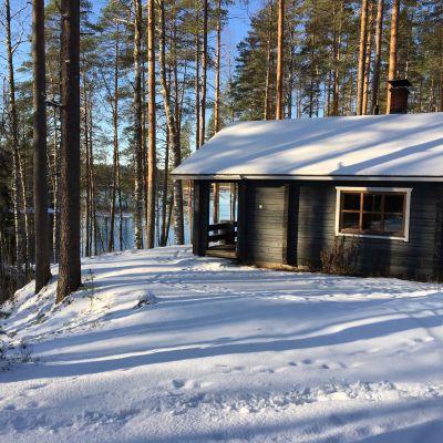 Mökki talvisessa jokimaisemassa Ruunaan luonnonsuojelualueella Lieksassa.
