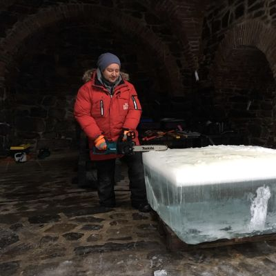 Jussi Miettinen sahaamassa jääkuutiota moottorisahalla Olavinlinnan sisäpihalla.