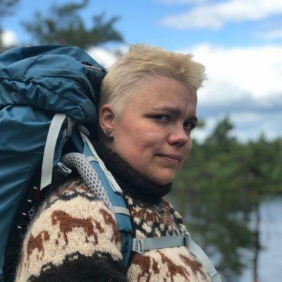 Nainen lähikuvassa sininen rinkka selässä, katsoo kameraan, taustalla näkyy järvi.