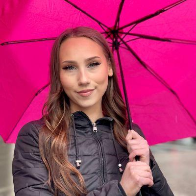 Nuori nainen, jolla n pitkät ruskeat hiukset ja upeasti meikatut silmät katsoo kameraan. Pään päällä on auki aniliininpunainen sateenvarjo.