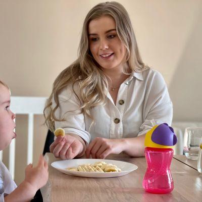 Pitkähiuksinen nainen ja taapero istuvat ruokapöydän ääressä. Nainen katsoo taaperoa ja ojentaa tälle banaanin viipaletta.