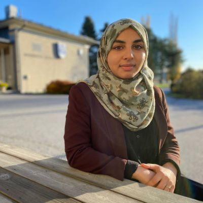 Sajal Maqsood på en bänk framför kommungården.
