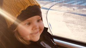Juuri leukemiasta parantunut pikkutyttö istuu raitiovaunun kyydissä. Aurinko paistaa ja tytön kasvoilla on innostunut hymynkare.