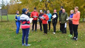 En kvinna står framför en grupp människor som lyssnar på henne. Alla är utomhus och har på sig sportiga höstkläder.