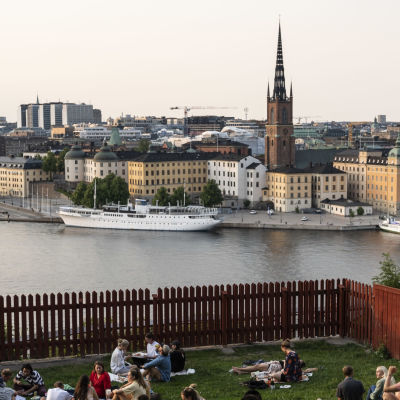 Människor sitter på gräsmattan i Ivar Los park i Stockholm och blickar ut mot stadens centrum en kväll i juli 2021.