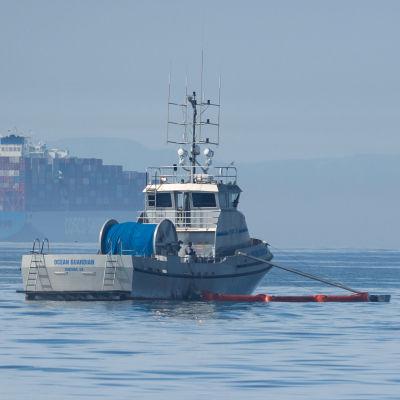 Båtar lägger ut bommar som ska hindra olja från att sprida sig i havet.