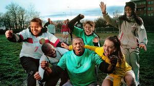 kuusihenkinen ryhmä jalkapallon harrastelijapelaajaa iloitsee etualalla, takana seisoo toinen joukkue paikoillaan
