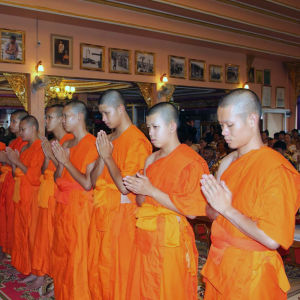 Pojkarna sitter i orange buddhistmunkskåpor i templet.