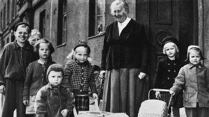 Miina Sillanpää omringad av barn.