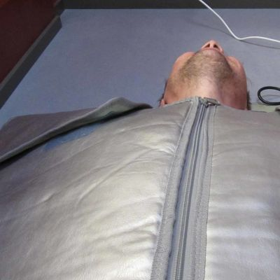 Kuvassa mies makaa infrapunamakuupussissa.