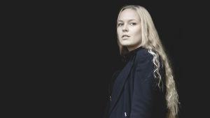 kvinna i ljus långt hår står mot en svart bakgrund