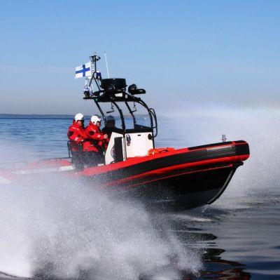 En röd gummibåt kör hårt på öppet hav.
