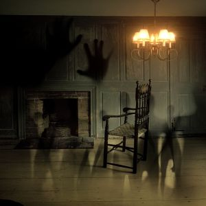 En tom stol i ett gammalt hus. Mörkar skuggor runt omkring.
